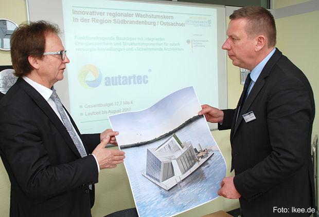 Amtsdirektor Gottfried Richter erläuterte im Gespräch mit Landrat Christian Heinrich-Jaschinski die Pläne für das neue schwimmende Selbstversorgerhaus am Bergheider See.