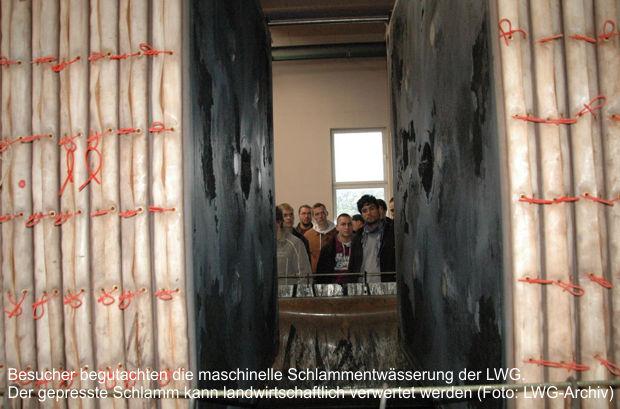 Besucher begutachten die maschinelle Schlammentwässerung der LWG. Der gepresste Schlamm kann landwirtschaftlich verwertet werden Foto: LWG-Archiv
