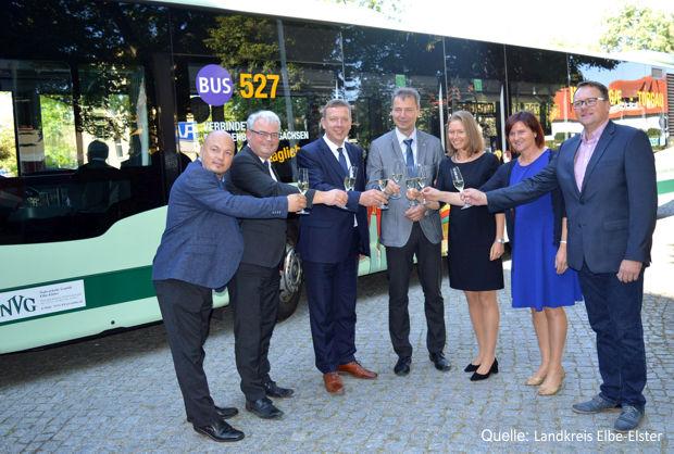 Ein Gläschen Sekt für unfallfreie Fahrten und zufriedene Gäste vor dem Linienbus der Tour 527.