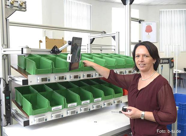 Die Projektleiterin Prof. Dr. Peggy Näser bei der Einrichtung eines ergonomisch gestalteten Montagearbeitsplatzes des Zentrums Effiziente Fabrik.