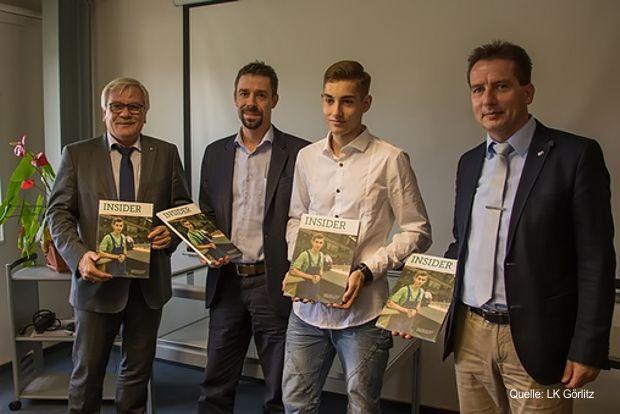 Robert Unger, Geschäftsführerin der Stahl- und Brückenbau Niesky GmbH (2.v.l.) und Auszubildender Maximilian Stephan nehmen den Atlas von Dr. Detlef Hamann (links) und Frank Großmann (rechts) entgegen.