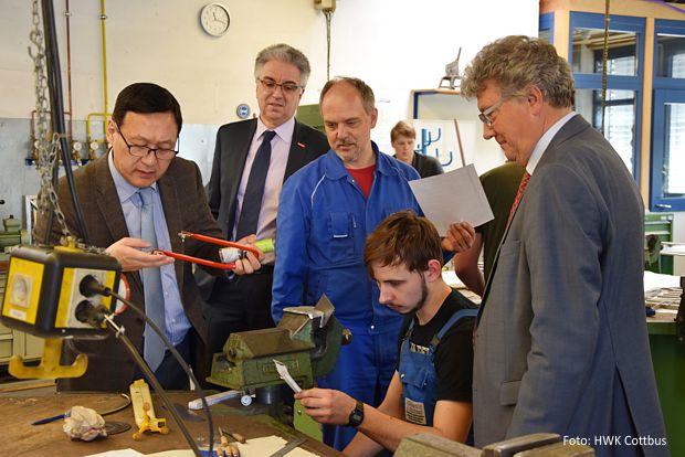 Dr. Damba Ganbat (l.), Botschafter der Mongolei, informierte sich über die Ausstattung der Werkstätten und die praktische Ausbildung von Metallbauern im BTZ Gallinchen. https://www.lausitz-branchen.de/medienarchiv/cms/upload/2018/april/Botschafter-Mongolei-BTZ-Cottbus.jpg